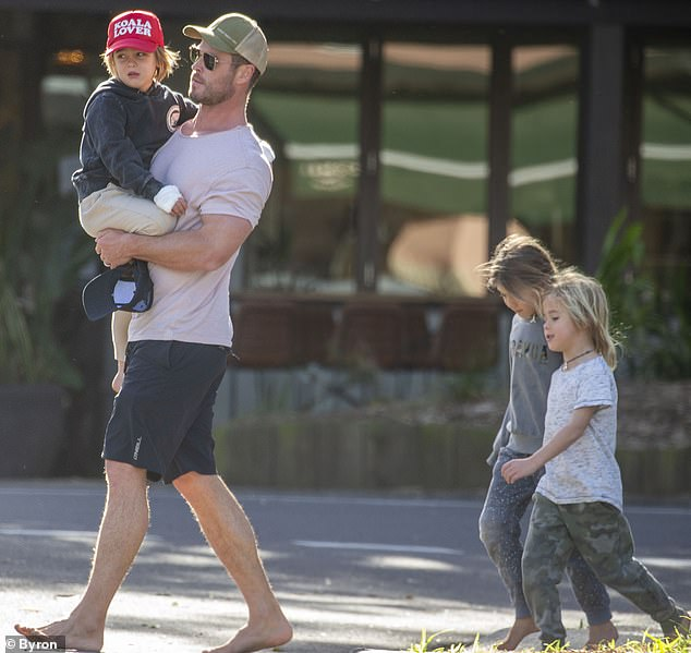 Super dad! Australian actor Chris Hemsworth was spotted carrying his injured twin son during barefoot stroll in Byron Bay with his three children on Thursday