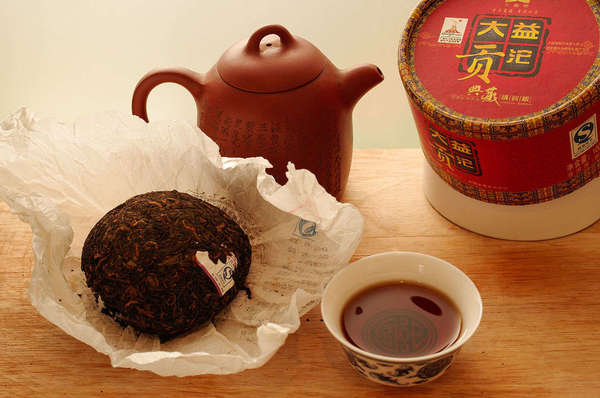 Compressed tea cake in paper wrapping, dark brown brewed cup of tea, clay teapot, and red cylindrical tea packaging