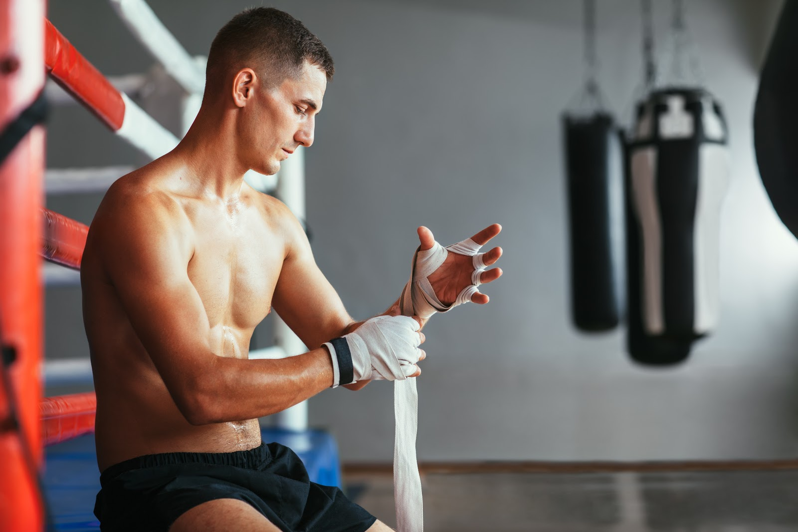 Shirtless man wrapping his hands sitting on the edge of the boxing ring a boxing gym.